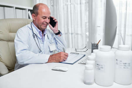 Smiling cardiologist checking cardiogram and consulting patient on the phone Imagens