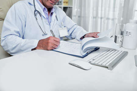 Cropped image of general pratitioner filling document with medical history of patient