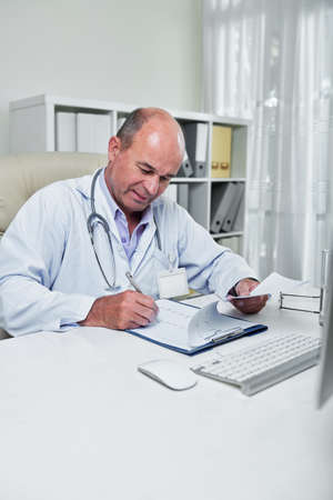 Serious experienced cardiologist sitting at table in his office and checking cardiogram of patient Imagens