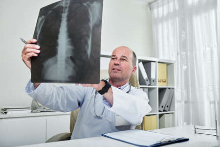 Mature general practitioner sitting with cardiogram on his table and looking at chest x-ray of patient Imagens