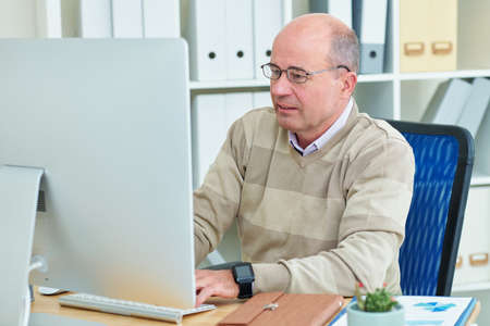 Mature financial manager in glasses working on computer at his office table