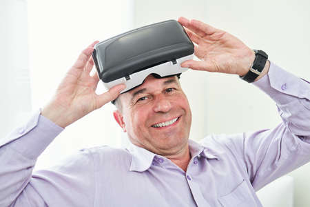 Happy mature man in shirt taking off virtual reality goggles after playing videogame