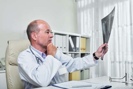 Pensive mature doctor looking at lungs x-ray of petient with pneumonia