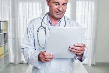 Frowning doctor in white labcoat reading medical history of patient