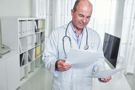 Serious frowning general practitioner reading document with medical tests results of patient