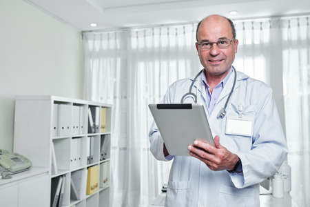 Portrait of smiling mature general practitioner in glasses holding tablet computer and looking a camera