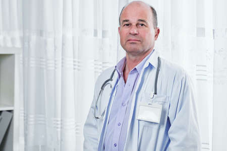Portrait of sad serious doctor in white labcoat with empty badge looking at camera