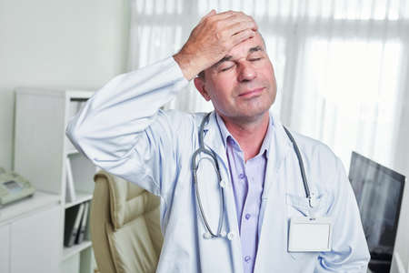 Smiling middle-aged doctor touching forehead with relief on his face Imagens