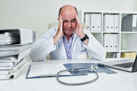 Sad frustrated mature general practitioner looking at opened folder with documents and stethoscope on his desk