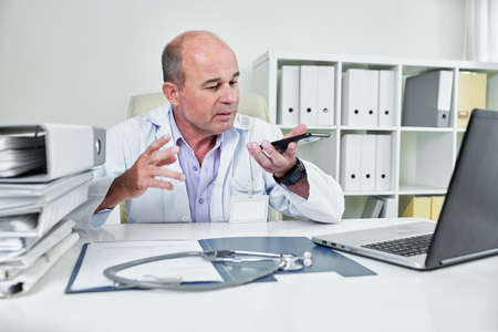 Serious general practitioner sitting at his office desk and recording audio message for patient Banco de Imagens