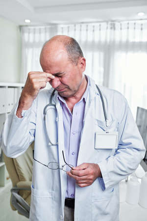 Stressed doctor suffering from severe headache after difficult day at work