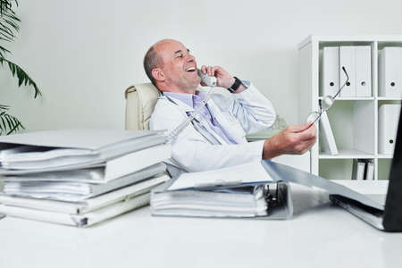 Happy doctor sitting at table covered with binders and folders and laughing when calling on phone Stock Photo