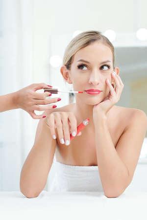Hand des Make-up-Künstlers, der roten Lipgloss oder flüssigen Lippenstift auf die Lippen einer hübschen jungen blonden Frau aufträgt