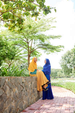 Happy muslim Asian female friends chating and joking when spending summer day together in city park 版權商用圖片