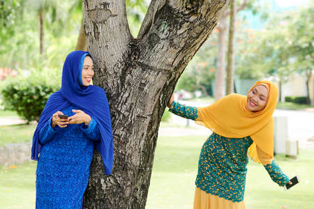 Cheerful young Asian woman in islamic dress leaning on tree trunk, texting and looking at her happy friend 版權商用圖片