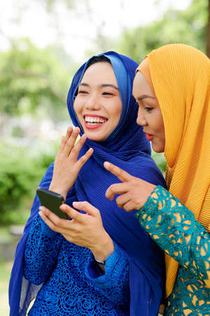 Two pretty muslim women laughing when reading text message from their friend on smartphone screen