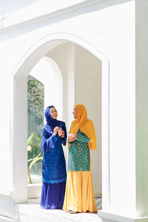Happy young muslim women standing in house entrance, talking and drinking delicious cocktails at party