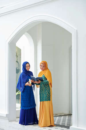Smiling pretty muslim women in traditional dresses reading holy quaran together 版權商用圖片