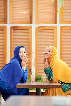 Happy young muslim women in bright dresses and hijabs meeting in cafe and enjoying sweet cocktails