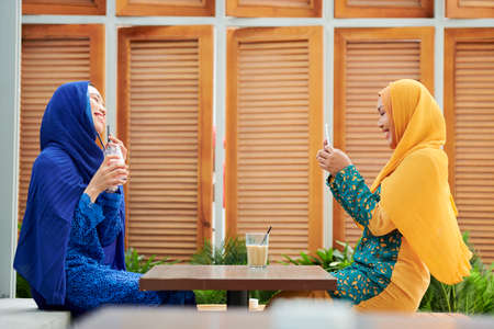 Cheerful young muslim woman in hijab taking photo of her friend with sweet milky cocktail on smartphone