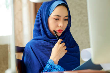 Pensive serious young beautiful muslim woman in blue hijab reading document and making corrections