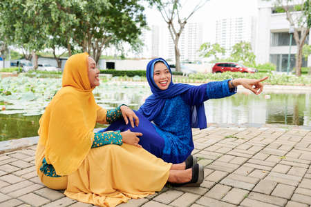 Smiling young Asian woman in islamic dress pointing at something funny to show it to her laughing friend sitting near by