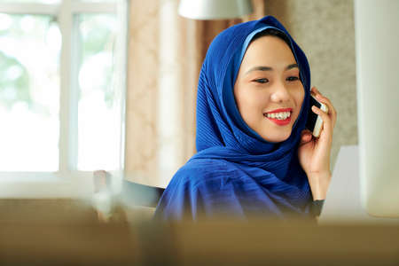 Portrait of happy young muslim woman in hijab reading e-mail on computer screen and talking on phone Stock Photo