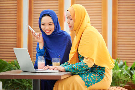 Young muslim businesswoman typing on laptop and discussing project with coworker