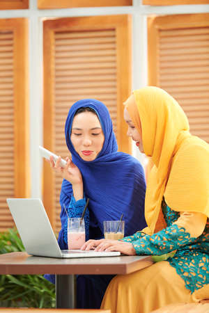 Pretty young muslim woman in hijabs talking and typing on laptop when working on project for university