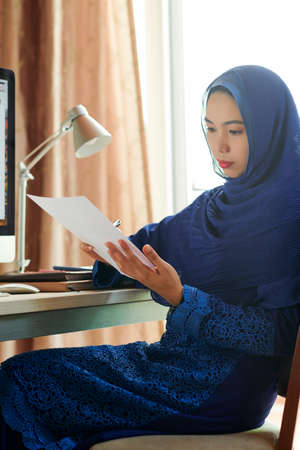 Serious pensive young muslim businesswoman sitting at office table and reading financial report