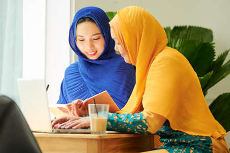 Positive muslim students reading book and typing on laptop when working on homework together 版權商用圖片