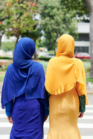 Rear view of yuong islamic women in traditional bright dresses walking outdoors