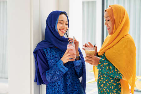 Pretty happy young Asian women in hijabs drinking delicious cold milk cocktails 版權商用圖片