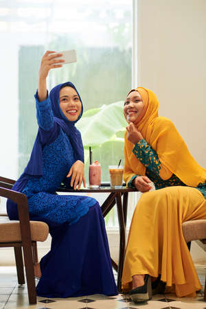Happy young Asian muslim woman taking selfie with her friend when spending time in cafe 版權商用圖片
