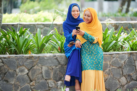 Pretty smiling young Asian woman in hijab showing photo on smartphone screen to her friend when thay are spending time in park