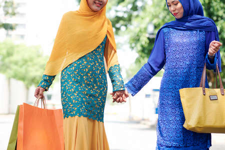 Positive young muslim women in hijab and beautiful dresses holding hands when walking outdoors after shopping in mall