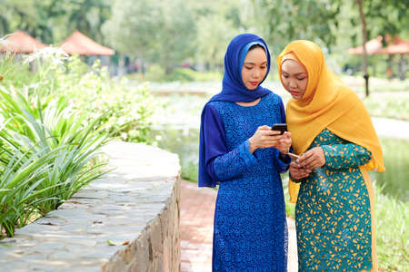 Pretty smiling young muslim woman in hijab showing new mobile application on her phone to friend when they are walking in park together 版權商用圖片