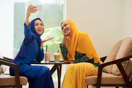 Happy young Asian women in hijabs and traditional dresses photographing in cafe