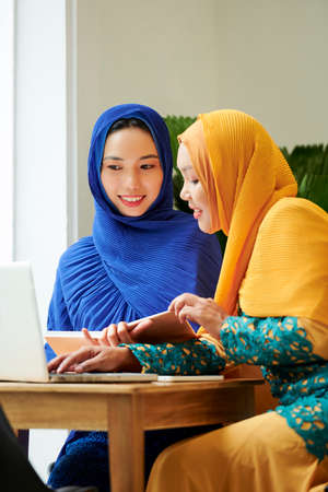 Smiling muslim women in traditional dresses and hijabs reading book and watching webinar on laptop