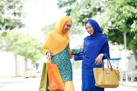 Pretty smiling Asian muslim woman complementing new dress of her friend after shopping together