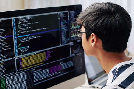 Intelligenter Teenager mit Brille, der den Programmiercode auf dem Computerbildschirm überprüft, wenn er an seinem Schreibtisch sitzt