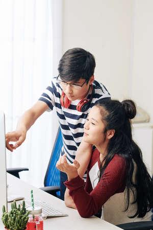 Smart Vietnamese teenagers discussing programming code on computer screen when working on school project 版權商用圖片
