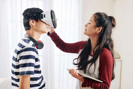 Teenage girl with tablet computer in hands helping brother to wear virtual relity heradset