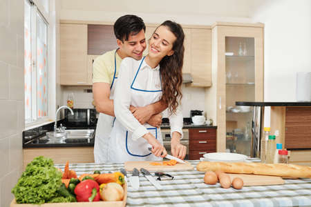 Happy handsome young man hugging from behind his girlfriend who is cooking dinner in kitchen