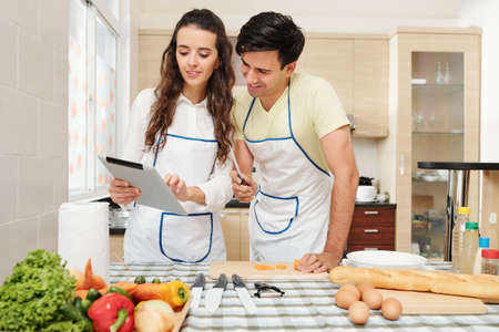 Positive young pretty woman showing recipe on tablet computer to her boyfriend when they are cooking together at home