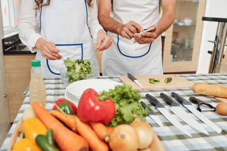 Woman in apron mixing healthy salad when her boyfriend answering text messages on his smartphone