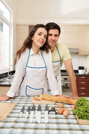 Cheerful young couple in white aprons standing at their kitchen table and smiling at camera