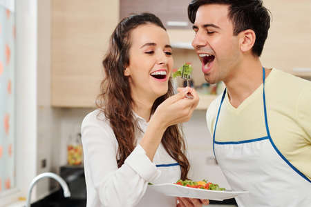 Pretty young woman asking husband to taste healthy salad she made for dinner