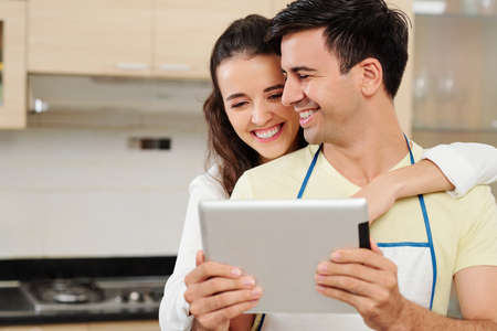Pretty smiling young woman hugging her boyfriend from behind and pointing at screen of digital tablet in his hands when that are standing in kitchen 版權商用圖片