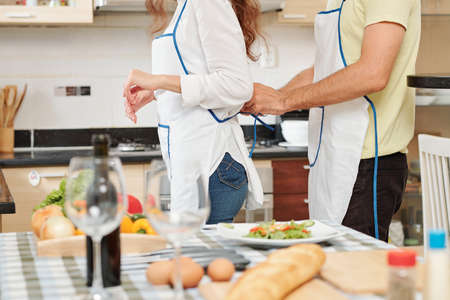 Cropped image of young couple getting reading to cook dinner at home and putting on aprons